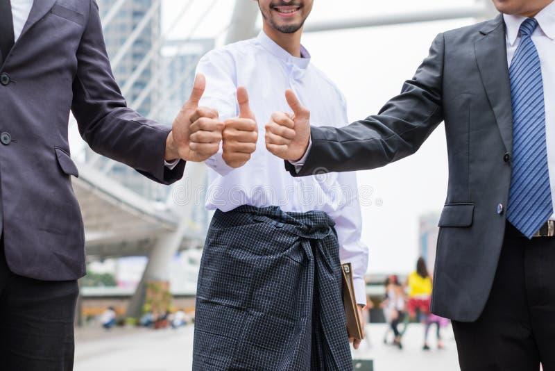 Trabalhos de equipa multirraciais do homem de negócios com doação dos polegares acima fotos de stock