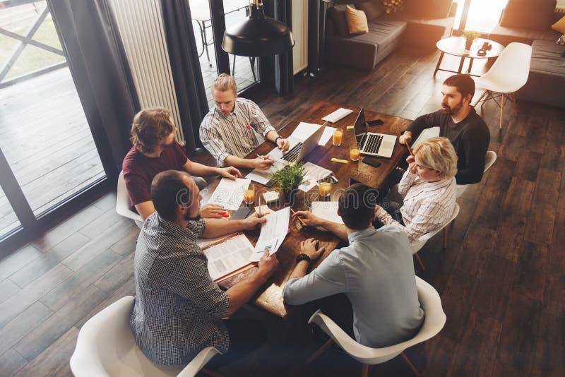 Trabalhos de equipa no projeto novo do negócio no espaço do sótão Colegas de trabalho do grupo imagens de stock