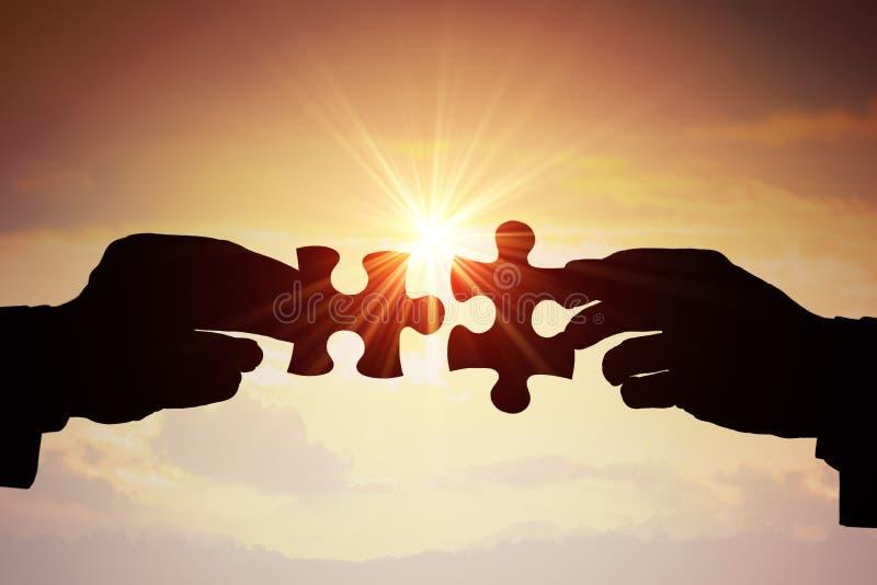 Trabalhos de equipa, parceria e conceito da cooperação Silhuetas de duas mãos que juntam-se a duas partes de enigma junto imagem de stock