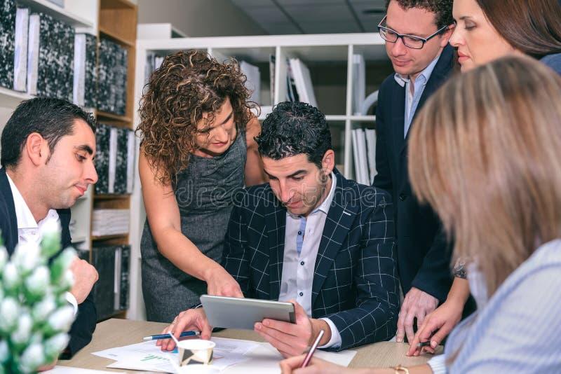 Trabalhos de equipa que olham o original de negócio na tabuleta eletrônica fotos de stock royalty free