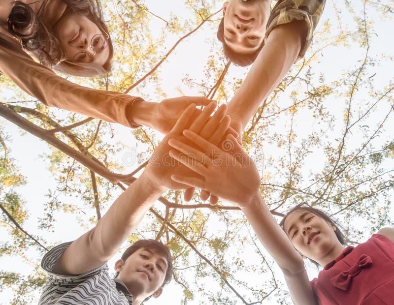 Trabalhos de equipe adolescentes dos estudantes da faculdade asiática que empilham o conceito da mão imagens de stock royalty free