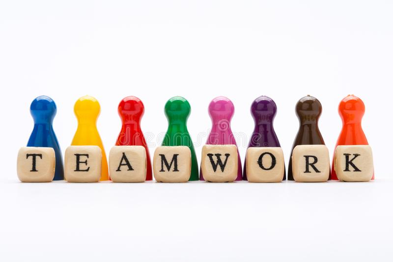 Trabalhos de equipe da palavra escritos em blocos e em penhores de madeira em várias cores no fundo branco fotos de stock