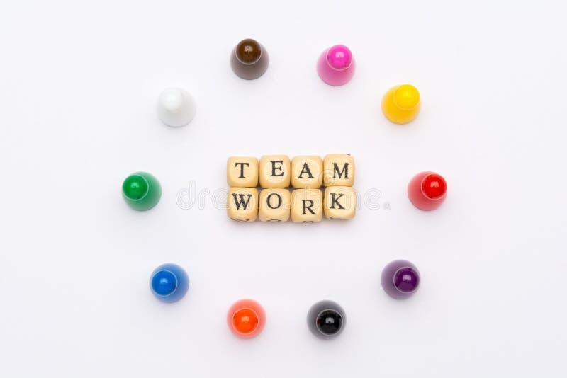 Trabalhos de equipe da palavra escritos em blocos e em penhores de madeira em várias cores no fundo branco fotografia de stock royalty free