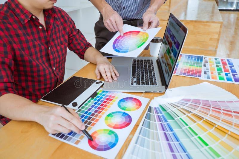 Trabalhos de equipe dos desenhistas criativos novos que trabalham no projeto junto e para escolher amostras da amostra de folha d fotografia de stock royalty free