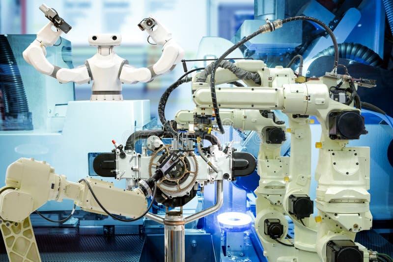 Trabalhos de equipe industriais da robótica que trabalham com as peças de motor na fábrica esperta foto de stock
