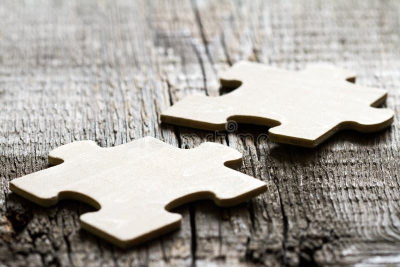 Trabalhos de equipe no conceito do sumário do negócio com enigma na placa de madeira foto de stock