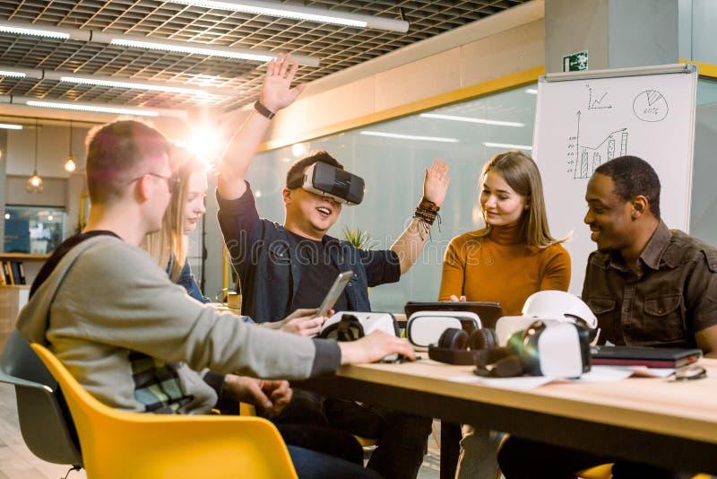 Trabalhos de equipe que tentam vidros da realidade virtual para o trabalho no escritório criativo Homem asiático novo que usa ócu imagens de stock royalty free
