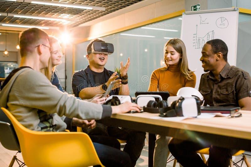 Trabalhos de equipe que tentam vidros da realidade virtual para o trabalho no escritório criativo Homem asiático novo que usa ócu imagens de stock