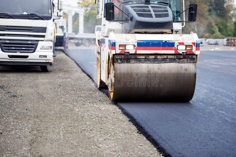 Trabalhos de estrada, asfaltando e colocando o betume fresco durante obras Compressor pesado industrial imagem de stock royalty free