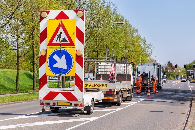 Trabalhos de estrada com caminhões e sinais de tráfego foto de stock
