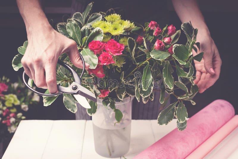 Trabalhos do florista Mãos das mulheres que fazem um ramalhete do casamento das rosas conceito da empresa de pequeno porte imagens de stock royalty free
