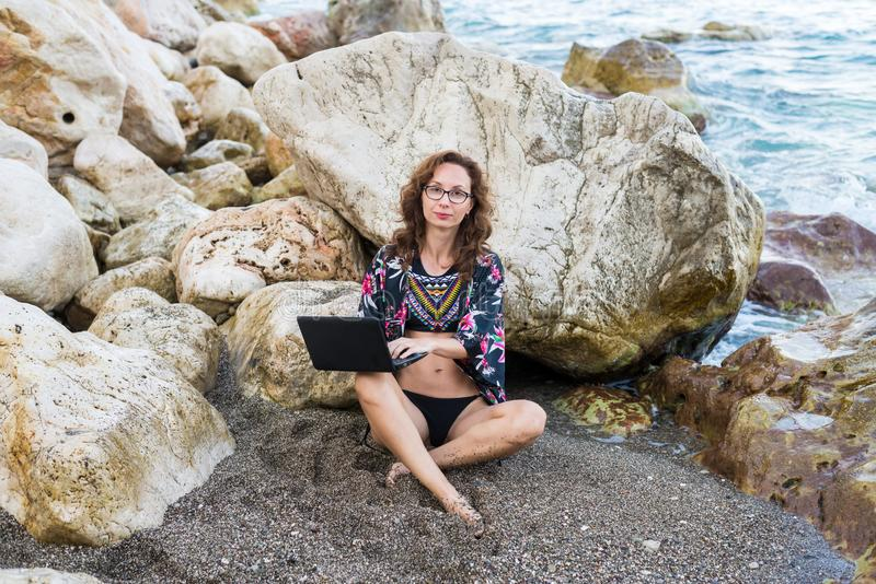 Trabalhos do viciado em trabalho da mulher no netbook que senta-se em uma pedra na praia imagens de stock royalty free