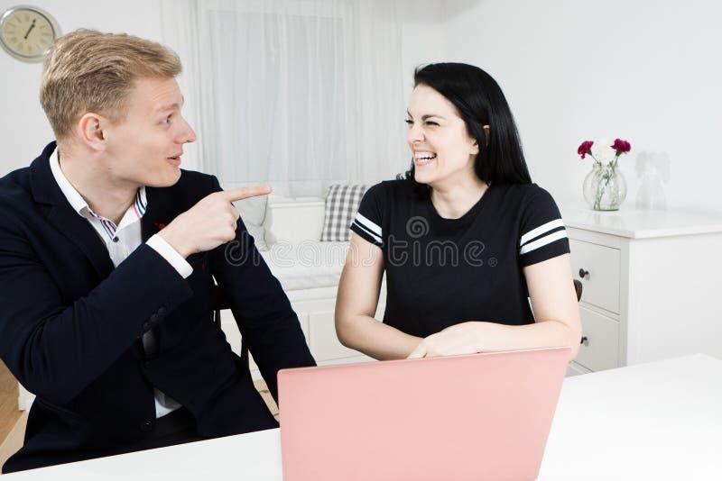 Trabalhos dos superiores com subordinado Dedo louro dos pontos do homem na mulher de cabelo preta imagens de stock royalty free
