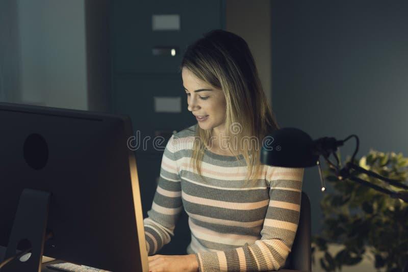 Trabalhos em rede sociais de sorriso novos da mulher com seu computador foto de stock