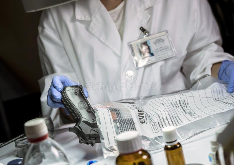 Tracce d'esame dell'ufficiale di polizia scientifico di pistola in laboratorio balistico fotografia stock libera da diritti