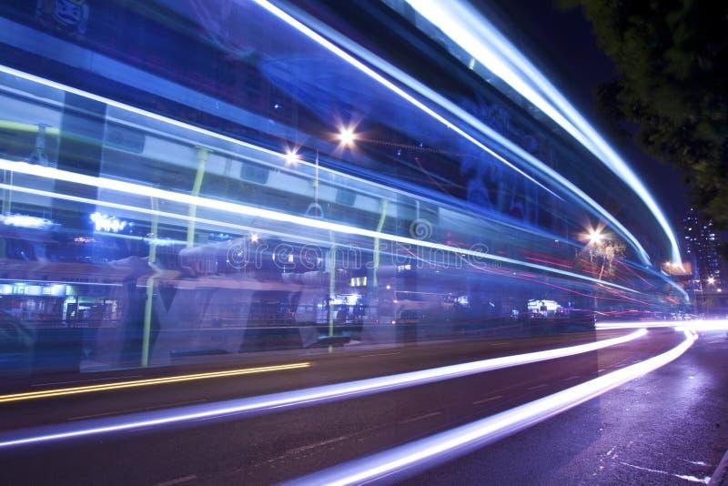 Tracce dell'indicatore luminoso alla notte con traffico occupato immagini stock