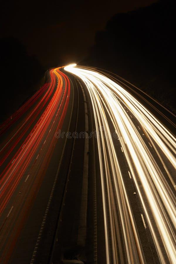 Tracce dell'indicatore luminoso su un'autostrada alla notte immagini stock libere da diritti