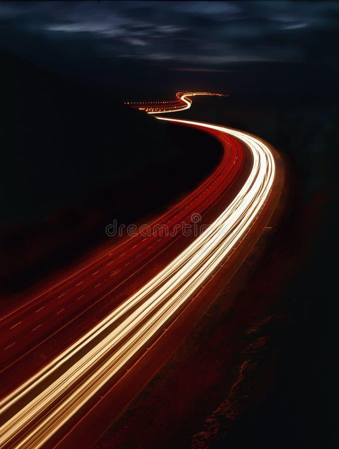 Tracce della luce lungo l'autostrada alla notte fotografia stock libera da diritti