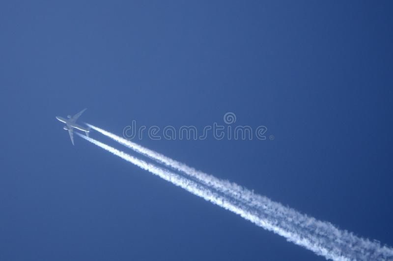 Traccia bianca di aereo attraverso il cielo blu L'aeroplano del getto sta volando su fotografie stock