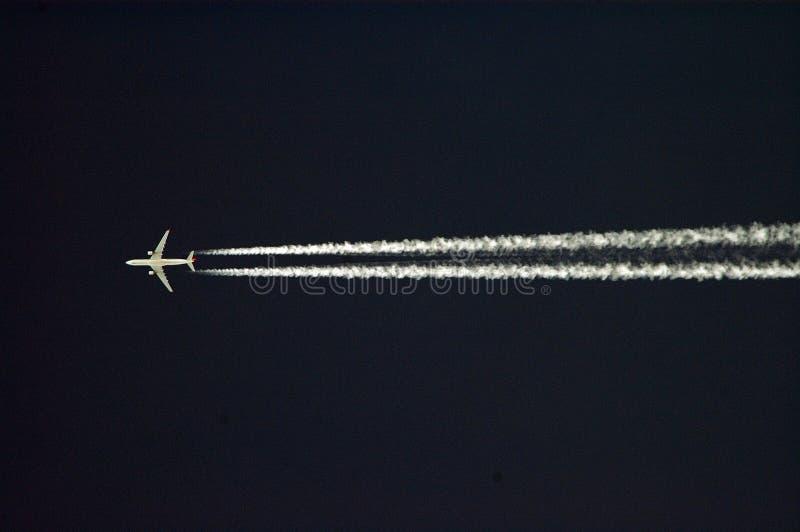 Traccia bianca di imbroglione sul cielo nero fotografia stock libera da diritti