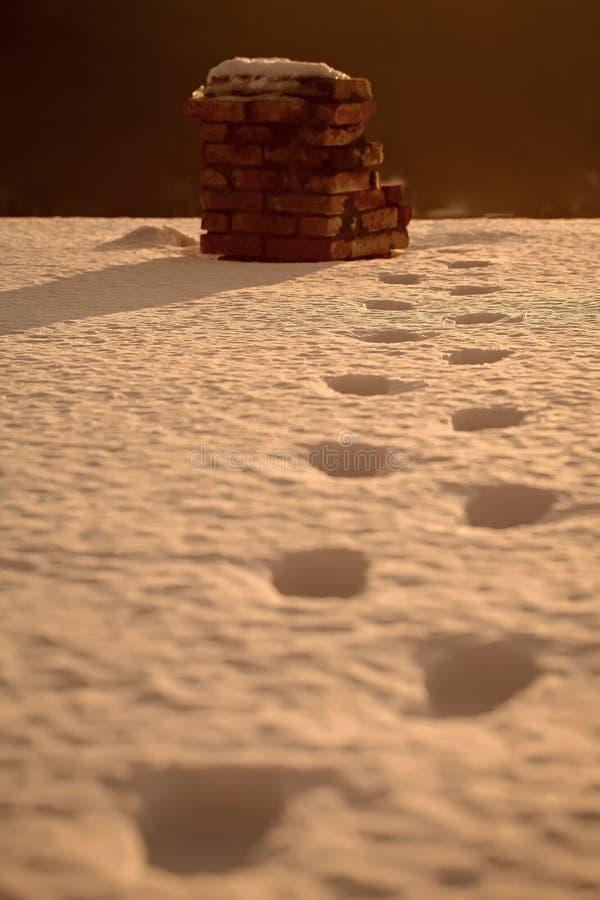 Traccia del piede di Babbo Natale su neve al camino del mattone immagini stock