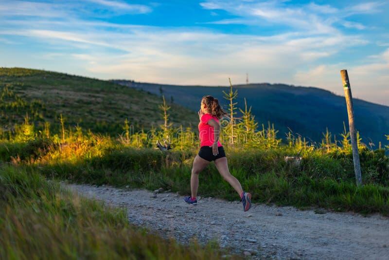 Traccia della giovane donna che corre in montagne all'estate immagini stock