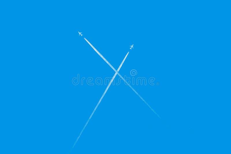 Traccia delle foglie degli aeroplani su chiaro cielo blu La vista da sotto sulle tracce da molti spiana Corsa fotografie stock