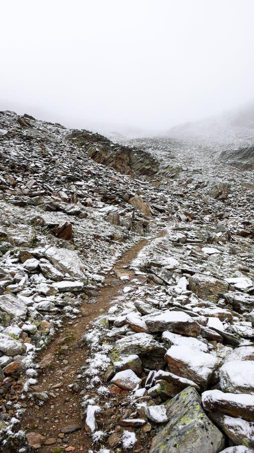 Traccia di escursione vuota che conduce nelle montagne alpine nevose e rocciose fotografie stock