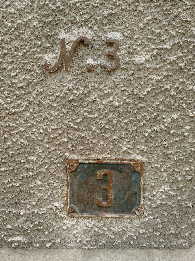 Traccia il muro di una vecchia casa con due diversi tipi di carattere numero 3 segni di indirizzo immagini stock libere da diritti