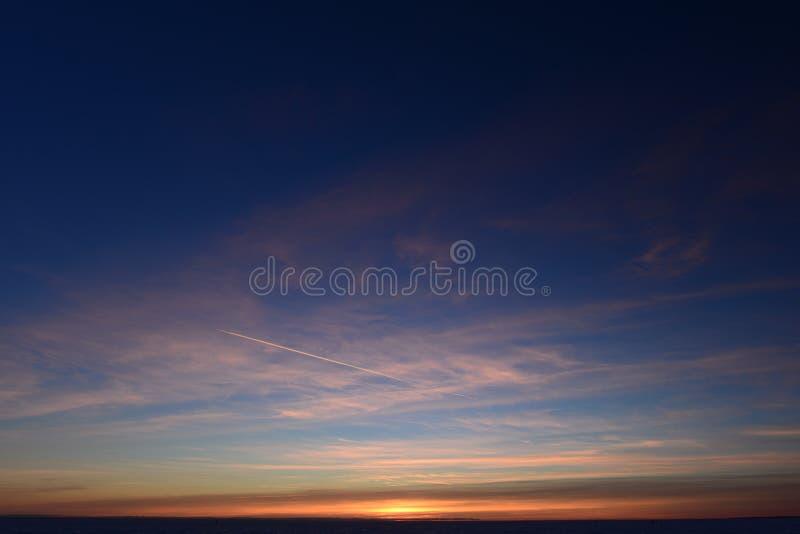 Tracciato aereo nel cielo azzurro in cerchio bianco in inverno al tramonto immagini stock