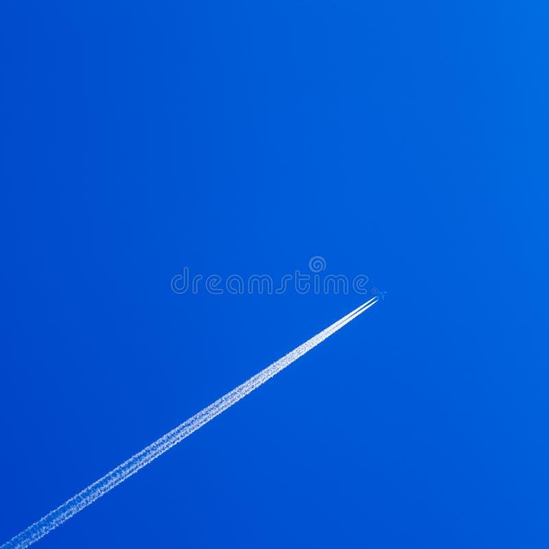 Trace blanche de contrail d'avion sur le ciel bleu photos libres de droits