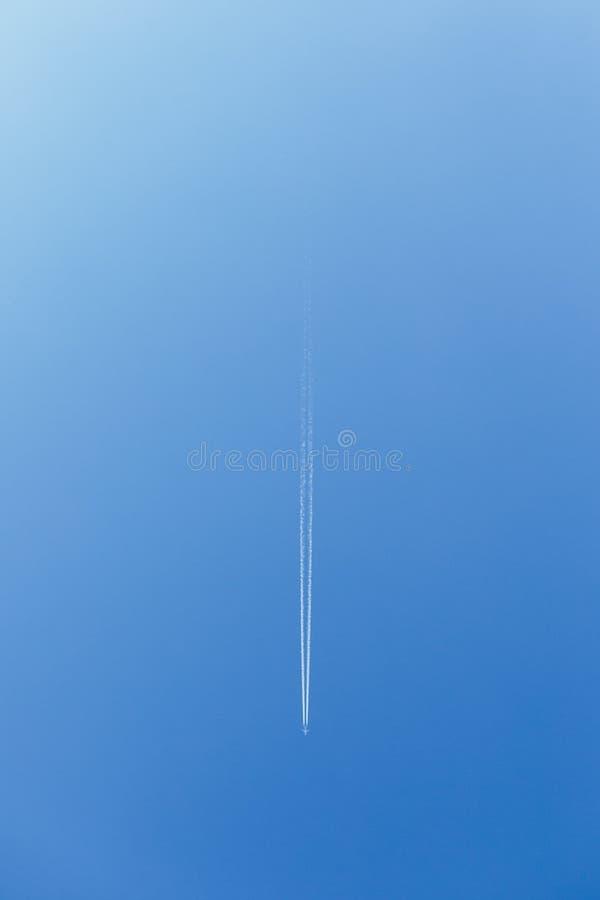 Trace blanche de fumée d'avion volant Image verticale Vol plat dans le ciel bleu et la ligne blanche vivante fumée de voie A?rone image libre de droits