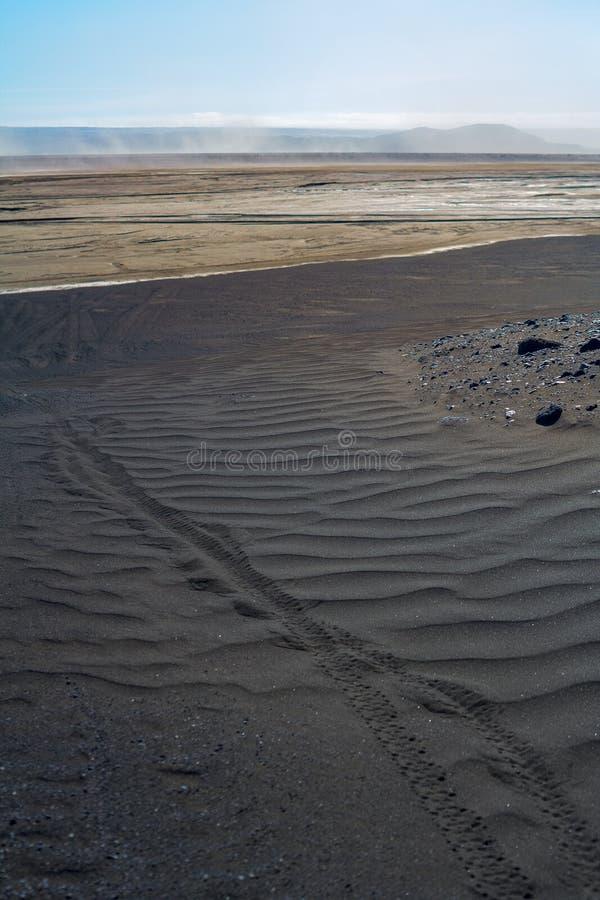 Trace des roues de bicyclette sur le sable noir de lave photographie stock libre de droits