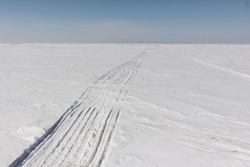 Trace of a snowmobile and sled on a snowy surface of frozen reservoir, Siberia, Ob River stock photography