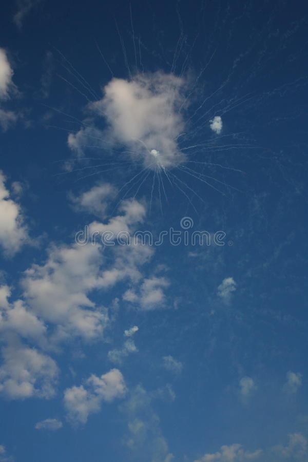 A trace of white pyrotechnic fireworks among the white clouds in the blue sky royalty free stock photos