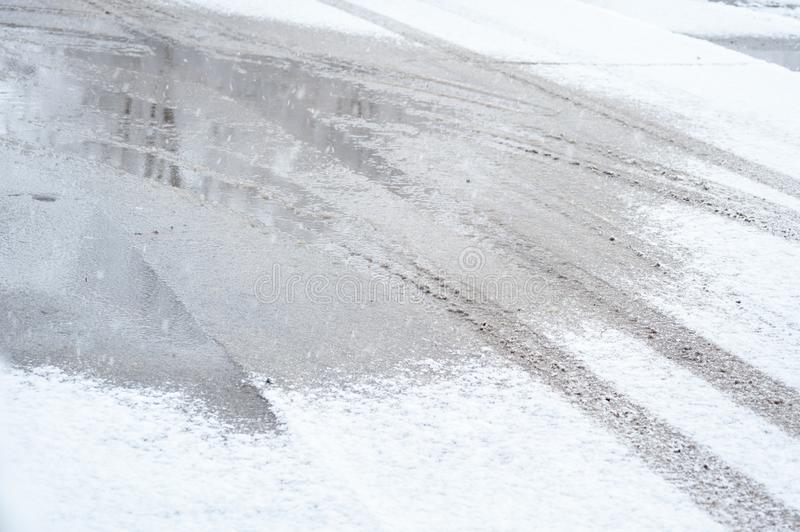 Traces of car tires in the snow on the road in the cold winter day royalty free stock photography