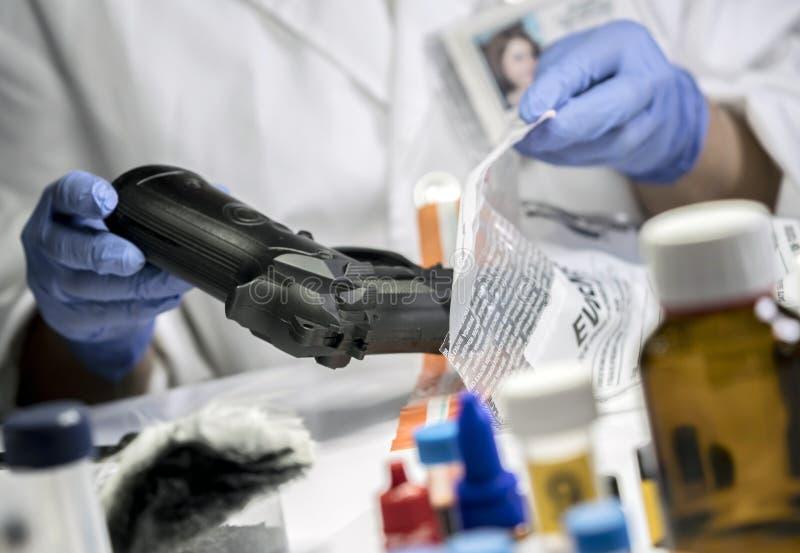 Traces de examen scientifiques de policier d'une arme ? feu dans le laboratoire ballistique photographie stock