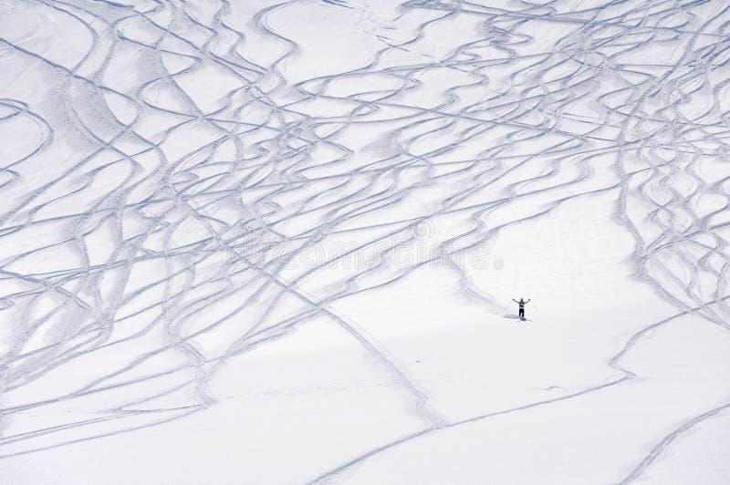 Traces de ski et une petite figure de skieur de freeride image libre de droits