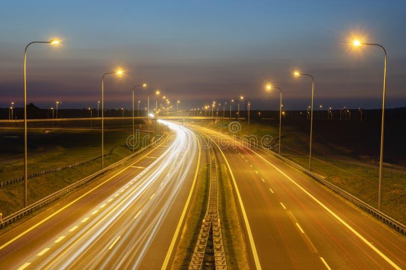 Traces des lumières sur la route de nuit image libre de droits