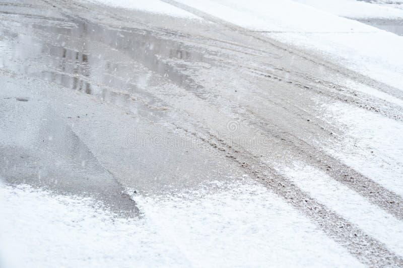Traces des pneus de voiture dans la neige sur la route pendant le jour d'hiver froid photographie stock libre de droits