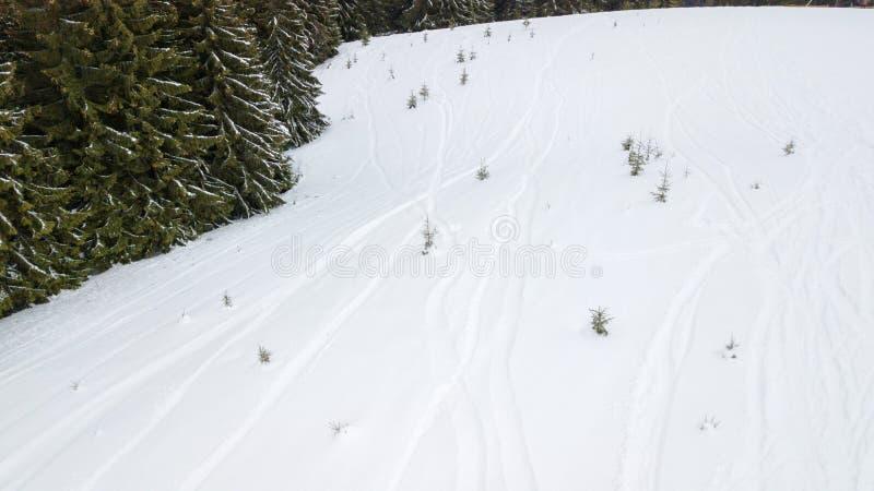 Traces des surfeurs et des skieurs dans la neige dans les montagnes photographie stock