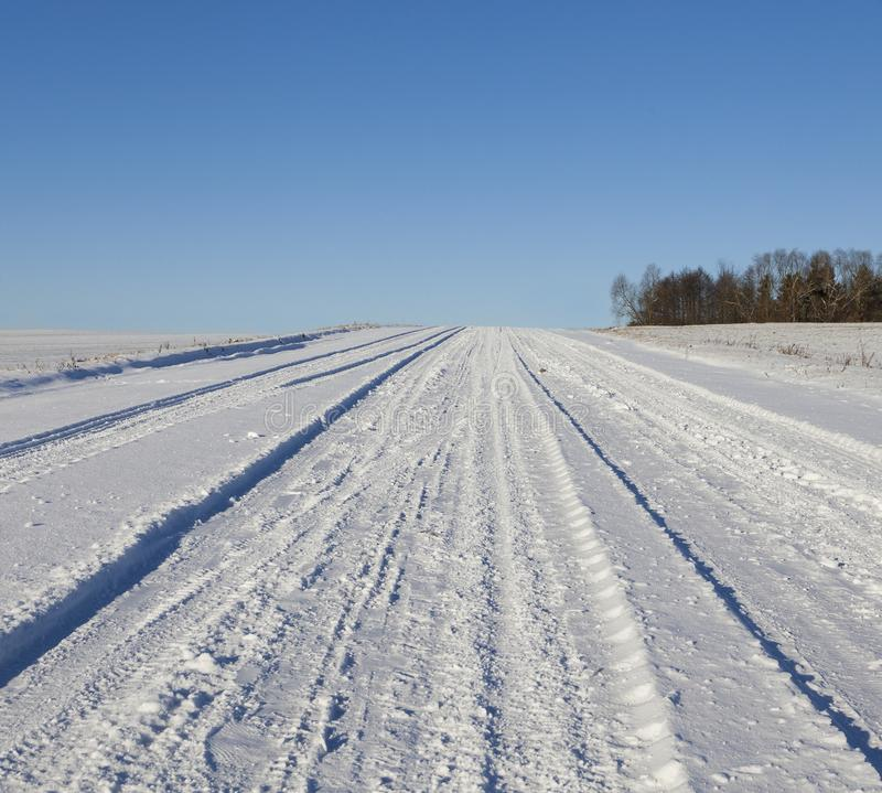 Ruts on road. Traces on the roadway in the snow, winter landscape with blue sky on a sunny day. On the drifts of the machine, deep ruts stock images