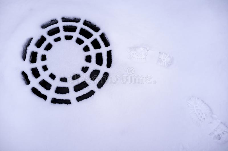 Traces of shoes on the snow to reach the metallic lid of sewage that looks like a spider web, and then disappear, as if someone stock images