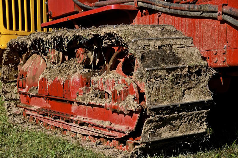 Track of a bulldozer caked with mud. An old red bulldozer has a track caked with mud, dirt, and clay royalty free stock photo