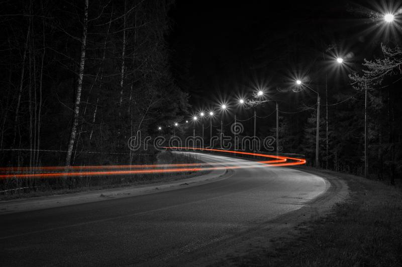 Track from the headlights of a passing car on the night road. The trail from the headlights of a passing car on the night road on a long exposure stock photos