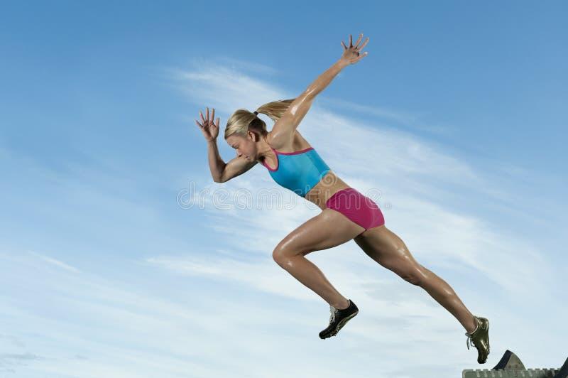 Track runner bursts off starting block royalty free stock photos