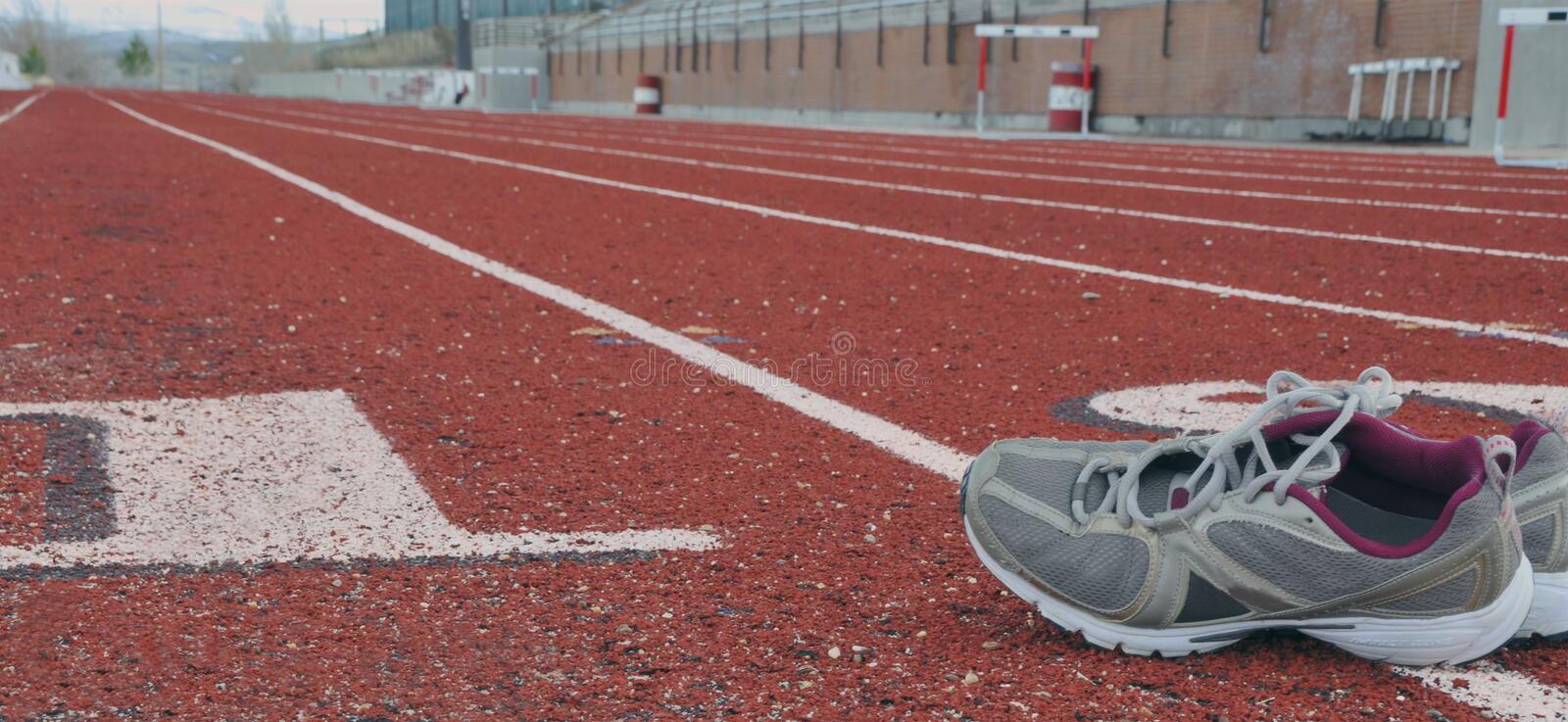 Track&shoes. Track with running shoes in lane, ready for practice stock photos