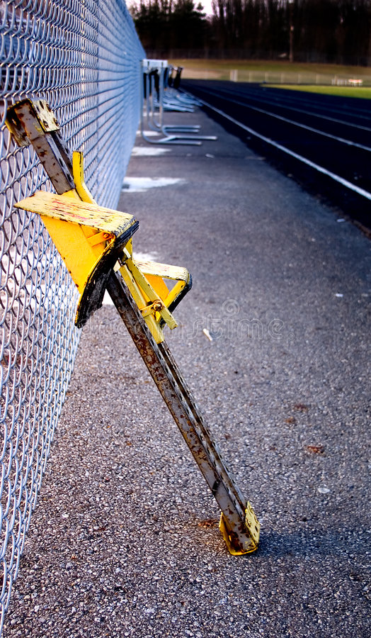 Track starting block leaning on fence royalty free stock photography