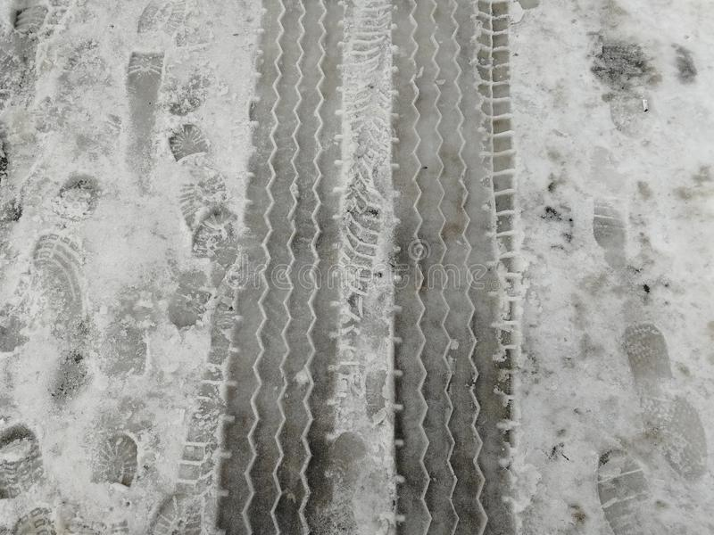 Track from the tread of the wheel of a truck and traces of shoes. In the winter royalty free stock photos