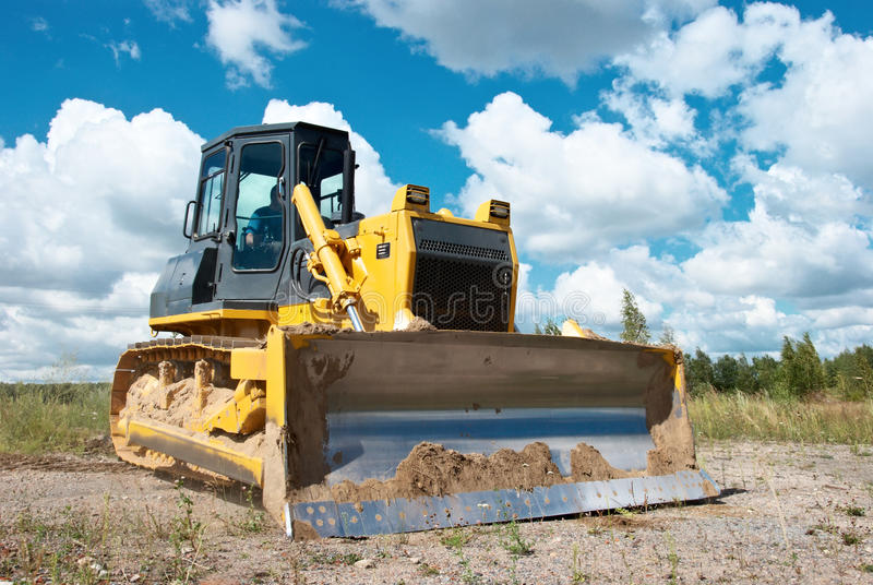 Track-type loader bulldozer excavator at work. Track-type loader bulldozer excavator machine doing earthmoving work at sand quarry royalty free stock photos